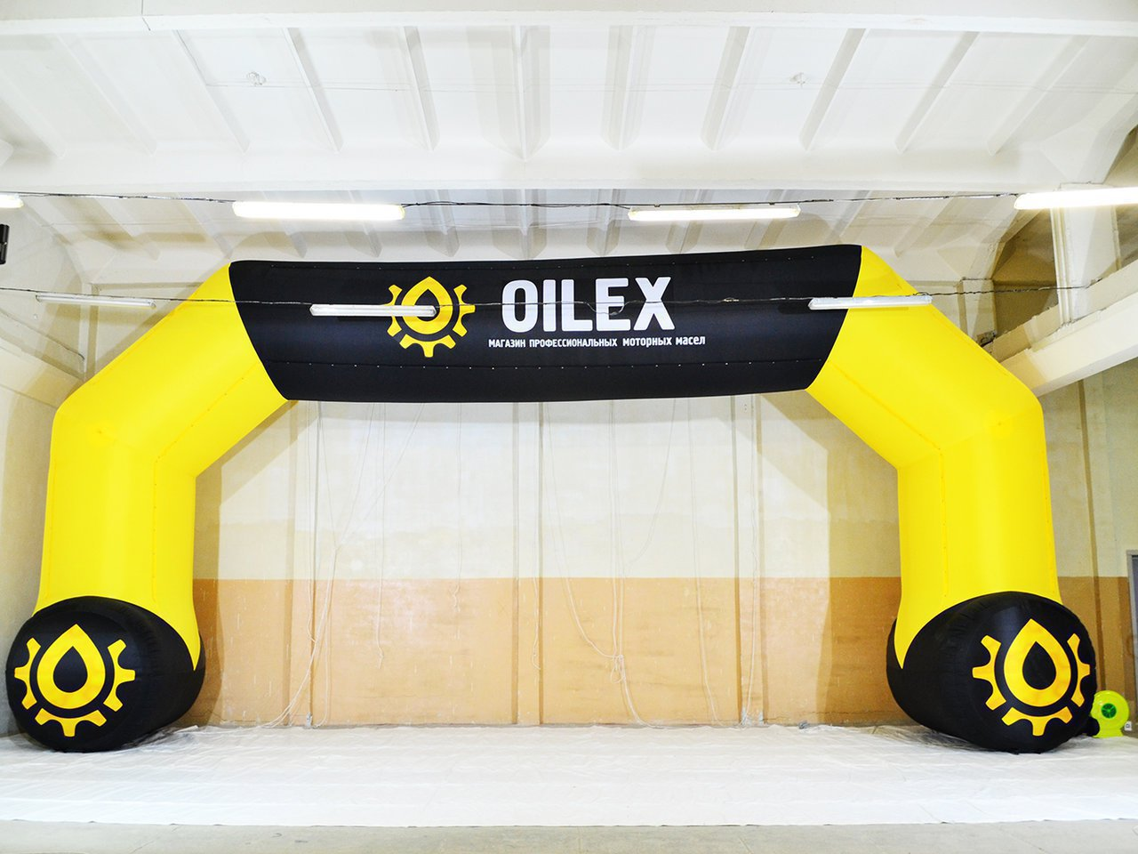 Inflatable arch with supports for a professional motor oil store
