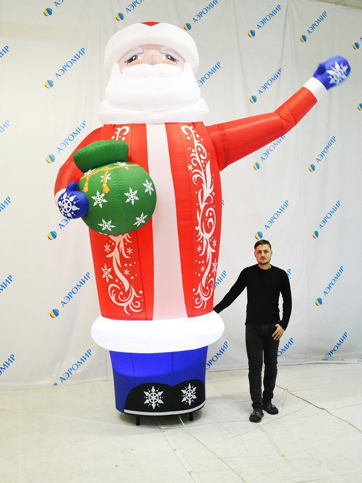 Inflatable Santa Claus with a gift and waving his hand